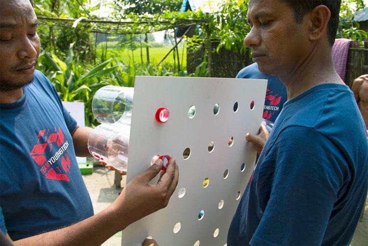 """Tình nguyện viên đang """"lắp đặt"""" điều hòa không cần điện năng cho các hộ dân Bangladesh."""