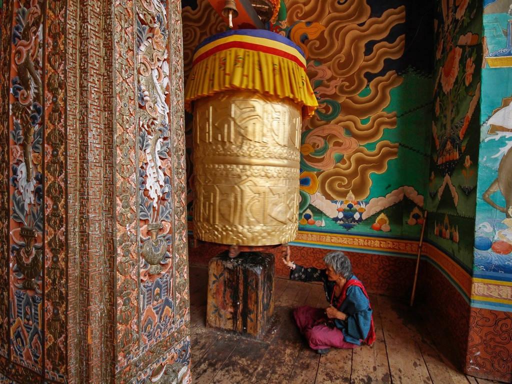Một cụ già quay kinh luân (bánh xe cầu nguyện) ở ngôi đền tại Punakha, phía tây Bhutan. Các kinh luân được chạm trổ tỉ mỉ với hàng nghìn câu thần chú. Người địa phương cho rằng quay bánh xe cũng như đọc những thần chú này hàng nghìn lần.