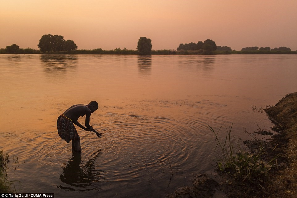 Một người phụ nữ của bộ tộc tắm ở sông Nile trong ánh hoàng hôn. Sau khi nội chiến kết thúc, hàng nghìn nam giới trở về Nam Sudan tìm vợ, khiến phụ nữ trở nên có giá.