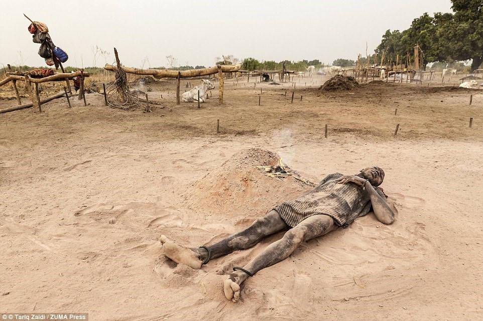 Người đàn ông này thư giãn trên lớp tro mềm mịn cạnh đống lửa phân bò đã gần tàn. Loại tro này mịn như bột talcum, bảo vệ cả người và bò khỏi cái nóng như thiêu như đốt của Sudan.