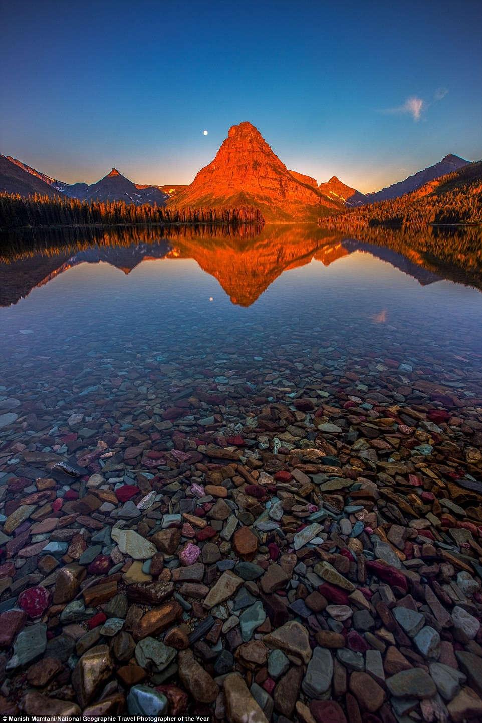 Bình minh trên hồ Medicine ở công viên quốc gia Glacier, Montana, Mỹ, với mặt nước phẳng lặng in bóng núi Sinopah.