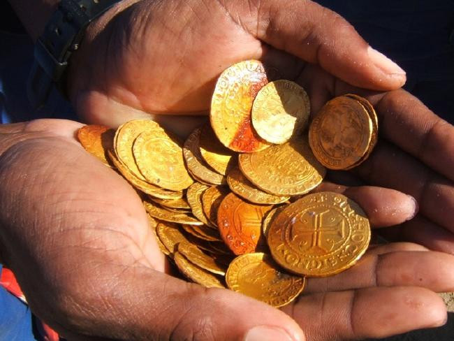 Nhà khảo cổ Dieter Noli cầm những đồng xu vàng tìm thấy từ xác tàu đắm.