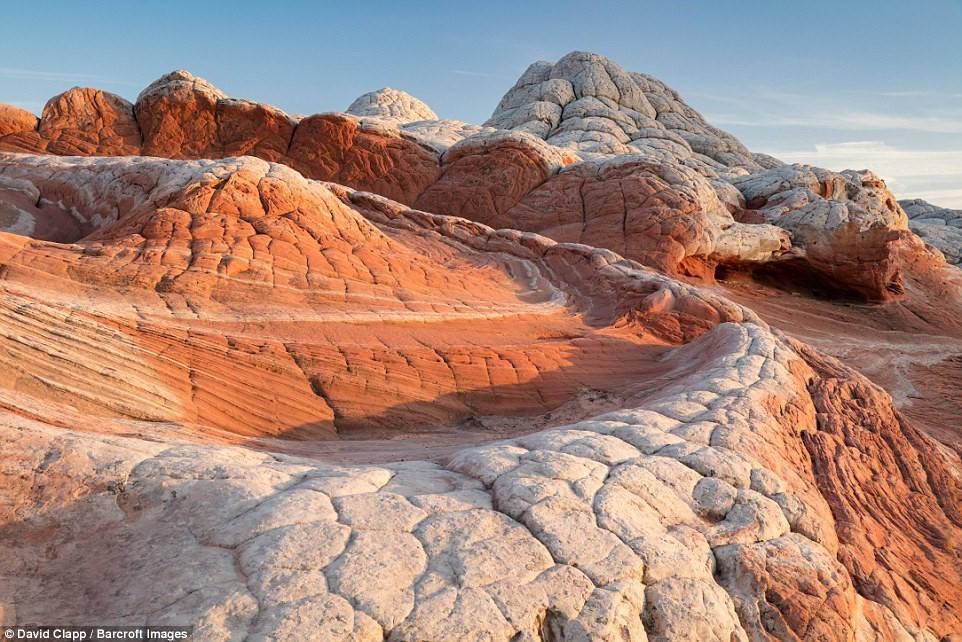 Khung cảnh White Pocket, Arizona, trong ánh bình minh, với sự tương phản mạnh mẽ giữa hai màu trắng và đỏ.
