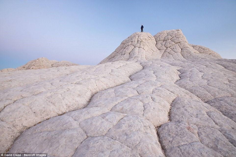 Một người đứng trên các tảng đá ở White Pocket, Arizona.