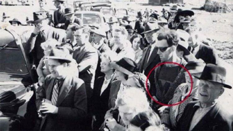 Người đàn ông đeo kính đen, ăn mặc thời trang hơn so với những người khác có mặt trong ảnh.