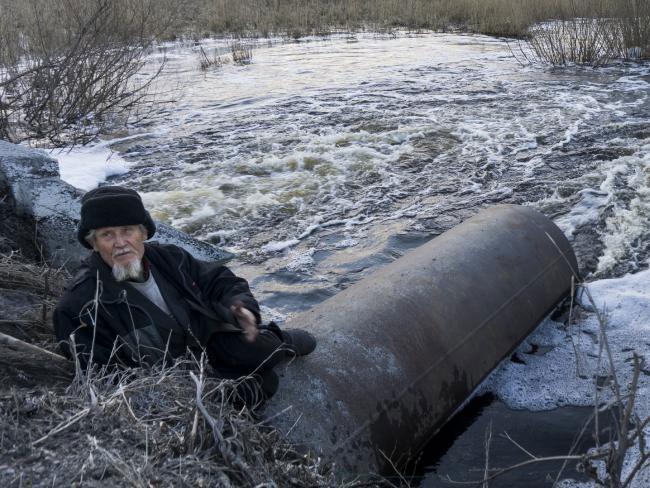 Một người dân thành phố câu cá bên con sông bị xả thải.
