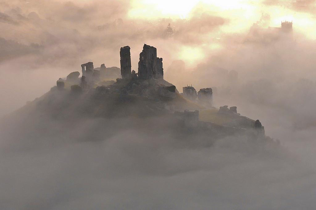 """Thoắt ẩn thoắt hiện trong làng sương mờ ảo là lâu đài Corfe nằm giữa đồi Purbeck thuộc vùng Dorset, mang đến một vẻ ma mị đến """"nổi da gà""""."""