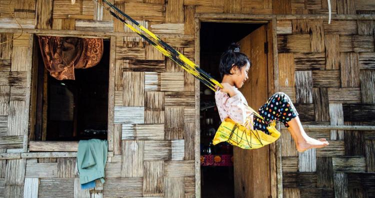 Sanjanai Kharrymba, 6 tuổi, chơi đùa trên chiếc xích đu tái chế ở trước cửa nhà.