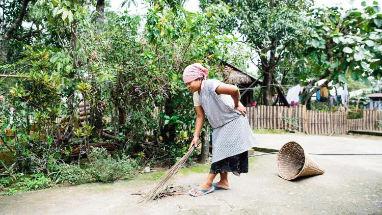 Một người phụ nữ đang quét rác vào giỏ rác hình phễu tại làng Mawlynnong.