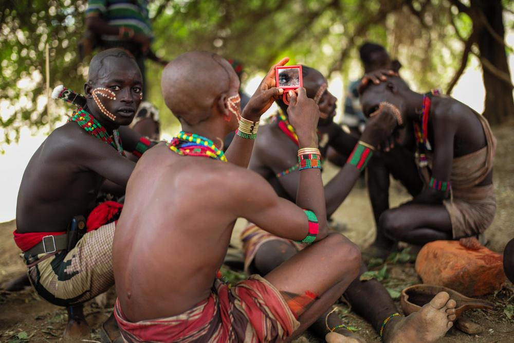 """Những người đàn ông tộc Hamar đang vẽ mặt, chuẩn bị cho buổi lễ """"nhảy bò""""."""