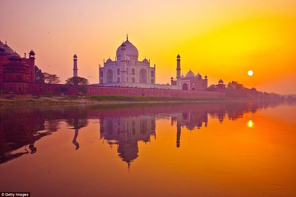 Khi mặt trời lặn sau lăng Taj Mahal của Ấn Độ, các mái vòm và tường cẩm thạch của công trình tuyệt mỹ này chuyển màu tím, giữa không gian lộng lẫy với ánh nắng màu cam ấn tượng.