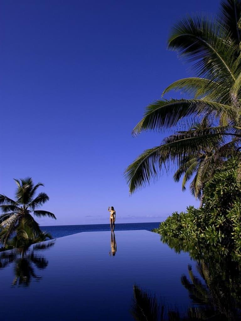 Chẳng còn gì bằng được ngắm nhìn bãi cát và biển từ bể bơi vô cực riêng và một ly cocktail trên tay ở Banyan Tree