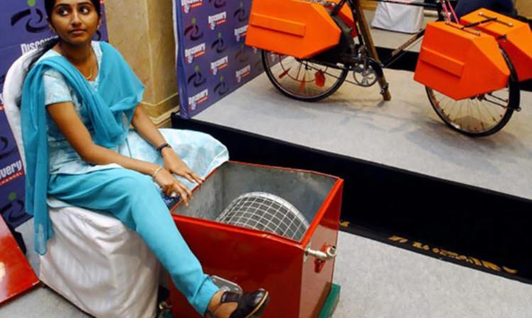 Remya Jose bên chiếc máy giặt chạy bằng bàn đạp của xe đạp.