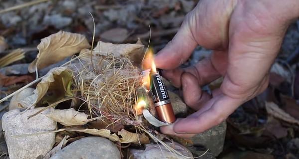 Dùng giấy gói kẹo cao su hoặc vỏ thuốc lá (loại phủ giấy bạc) rồi nối vào hai đầu âm dương của cục pin, bạn cũng có thể tạo ra lửa.