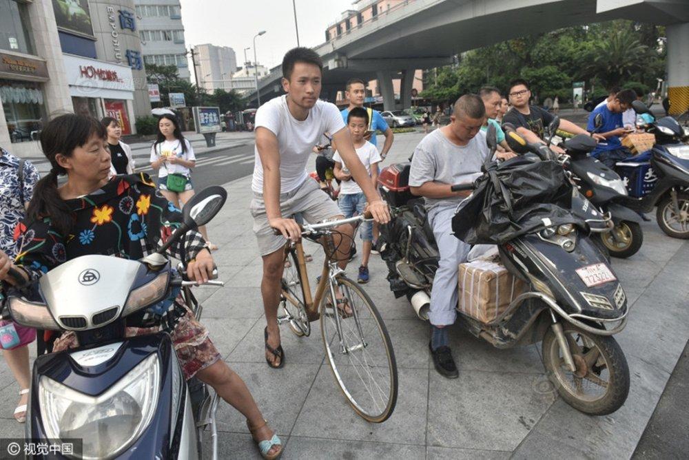 Abu sử dụng xe đạp tre trên đường, thu hút sự chú ý của nhiều người.