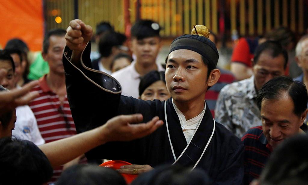 Thầy tu tung đồng xu để các tín đồ cầu may trong dịp lễ Ma Quỷ ở Malaysia.