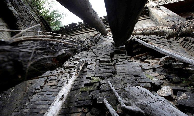 Bà Li Yonghua sử dụng thân cây để chống một bức tường nghiêng của ngôi nhà.