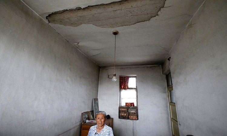 Bà Gao Xiuzhen, 81 tuổi, ngồi trong ngôi nhà hư hỏng cạnh một mỏ than ở làng Yongdingzhuang.