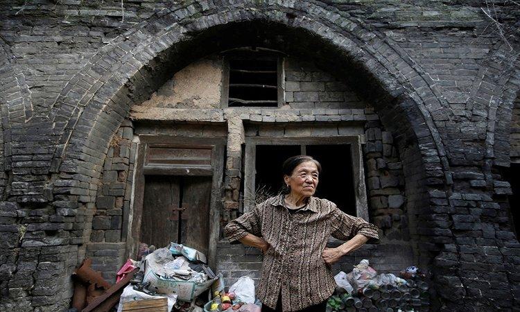 Bà Li Yonghua, 65 tuổi, đứng trước ngôi nhà bị hư hỏng tại khu vực sụt lún nằm cạnh một mỏ than ở làng Helin, ngoại ô thành phố Xiaoyi, tỉnh Sơn Tây.