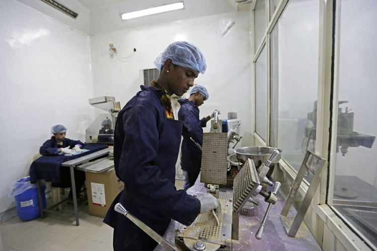 Công nhân chế biến nước tiểu bò trong một nhà máy của Trung tâm Y tế Liệu pháp nước tiểu bò tại thành phố Indore, Ấn Độ.