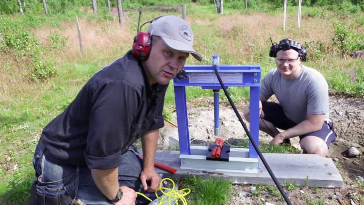 Hai người chuẩn bị làm thí nghiệm: dùng máy ép thủy lực ép lên khối thuốc nổ.