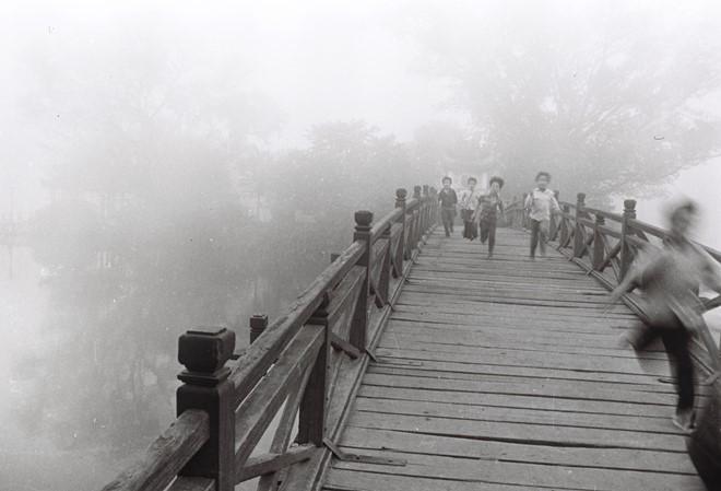 Những đứa trẻ nô đùa trên cầu Thê Húc dẫn vào đền Ngọc Sơn.