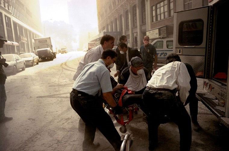 Các nhân viên y tế nhấc một nạn nhân ra khỏi cáng để đưa lên xe cứu thương chở tới bệnh viện.
