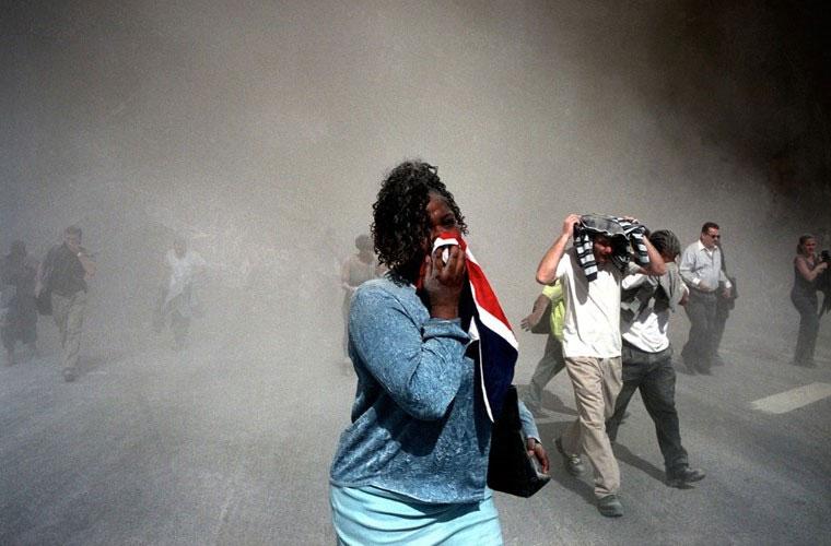 Người phụ nữ bịt kín mũi để bảo vệ mình trước đám tro bụi kín đặc sau khi 2 tòa tháp sụp đổ.