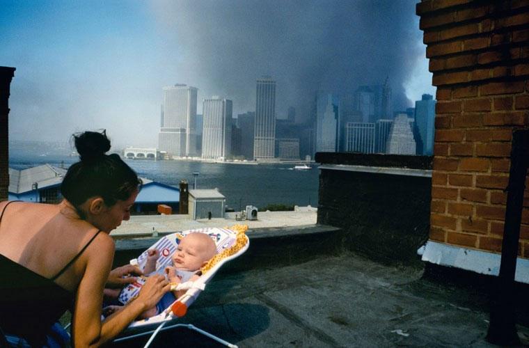 Bà mẹ trẻ dỗ dành con nhỏ trên tầng mái của một ngôi nhà ở Brookly