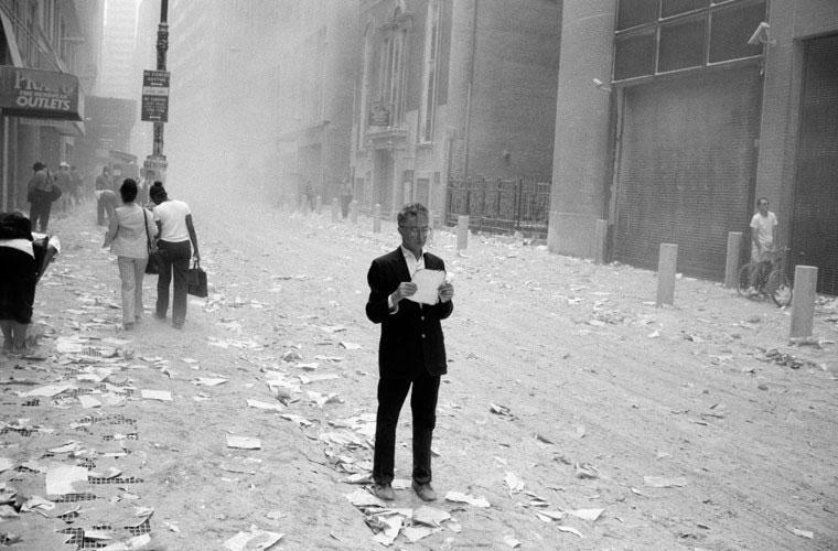 Người đàn ông choáng váng đang cầm trên tay một mảnh giấy bị hất văng từ hai tòa tháp.