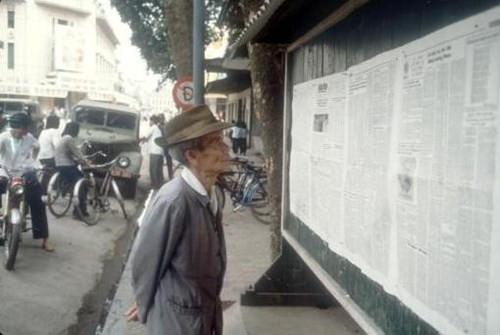 Một cụ già đọc báo dán tại một bảng tin trên phố Hàng Khay ở Hà Nội.
