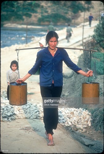 Người phụ nữ gánh nước tại một ngôi làng đang được tái thiết sau chiến tranh biên giới 1979.