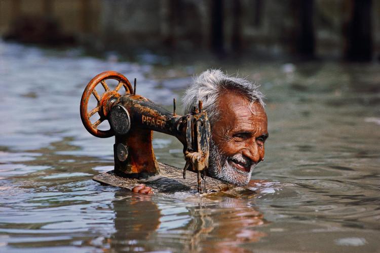 """Ông cụ người Ấn Độ """"cứu"""" chiếc máy khâu - nguồn sống của cả gia đình. Nụ cười của cụ vẫn tỏa sáng trong dòng nước lũ."""