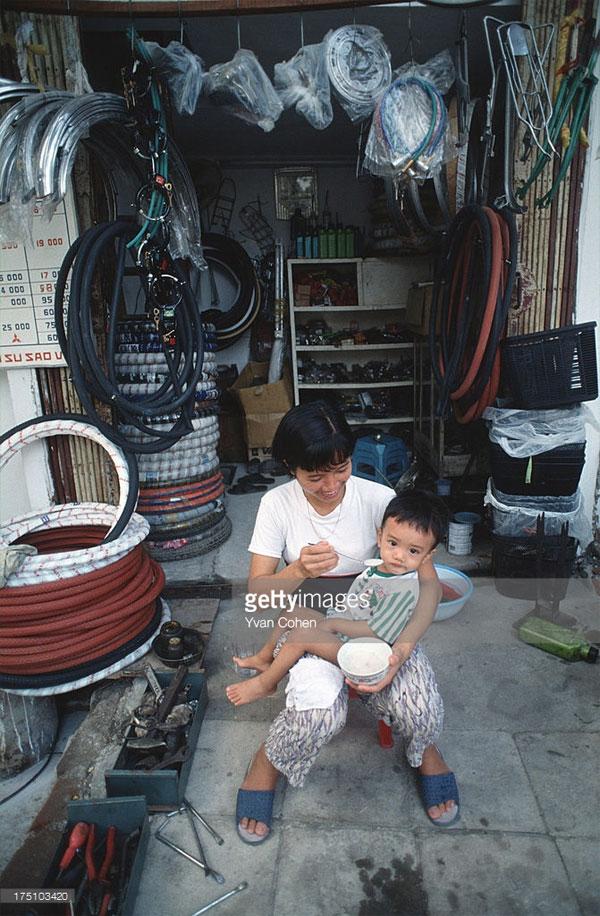 Người phụ nữ bón cho con ăn bên ngoài một cửa hàng phụ tùng xe đạp.