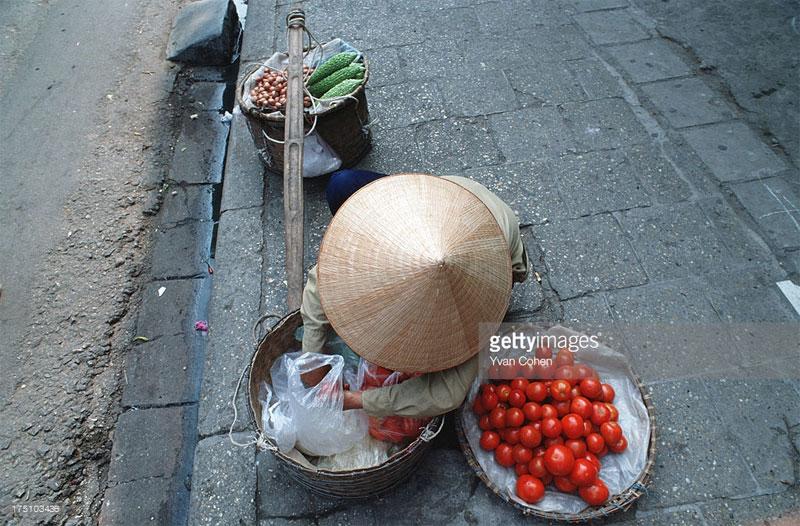Một người phụ nữ bán rau quả rong bên vỉa hè.