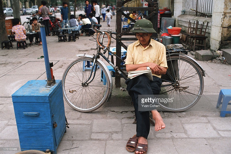 Người thợ sửa xe đọc báo trên hè phố Trần Hưng Đạo.