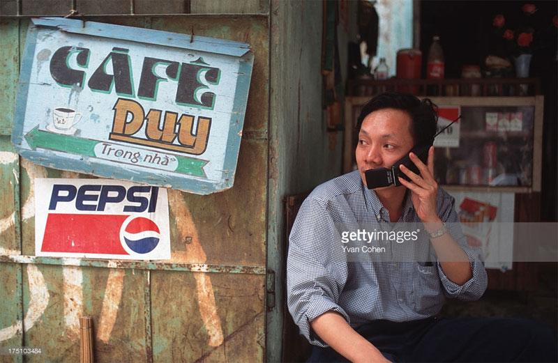 Một người đàn ông nói chuyện qua điện thoại di động tại một quán cà phê vỉa hè.