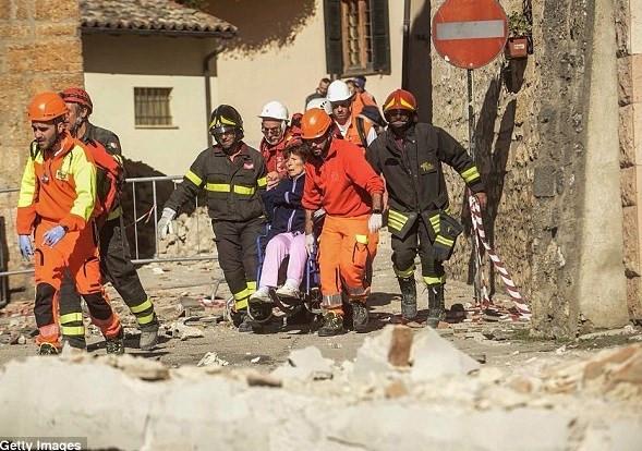 Lực lượng cứu hộ đưa một phụ nữ ngồi xe lăn ra khỏi một tòa nhà bị hư hại.