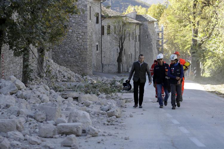 Các nhân viên cứu hộ đi qua một bức tường đổ sập ở Norcia.