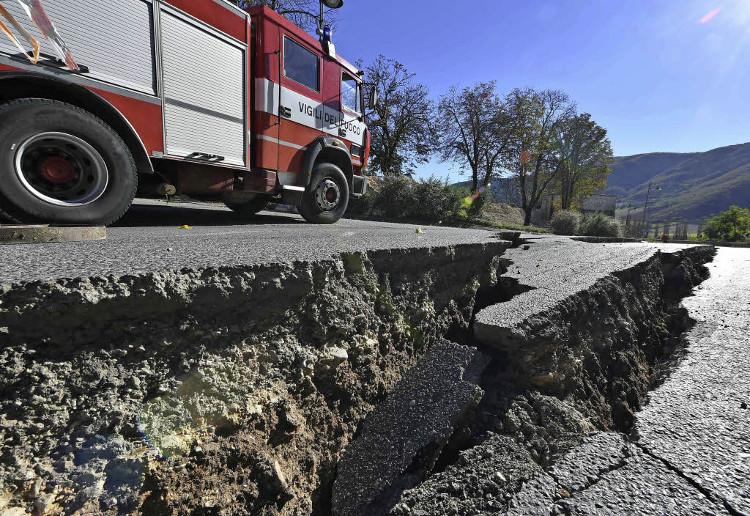 Lính cứu hỏa dừng lại để kiểm tra một vết nứt trên đường ở ngoại ô thị trấn Norcia sau động đất.
