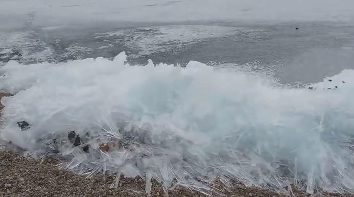 Cảnh tượng sóng xô vào bờ trong khi mặt nước vẫn bị đóng băng.