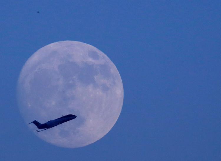 Máy bay bay ngang qua bầu trời Kathmandu ở Nepal, với hậu cảnh mặt trăng.