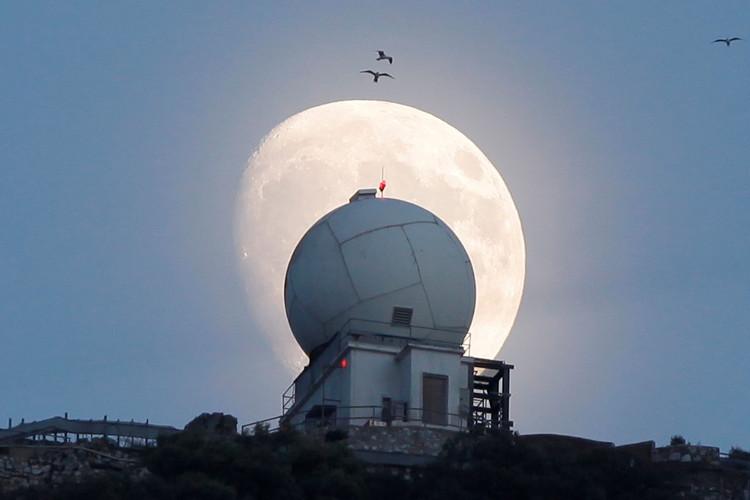 Trăng rằm dần xuất hiện trên nóc một tháp quan sát tại vùng lãnh thổ Gibraltar của Anh.