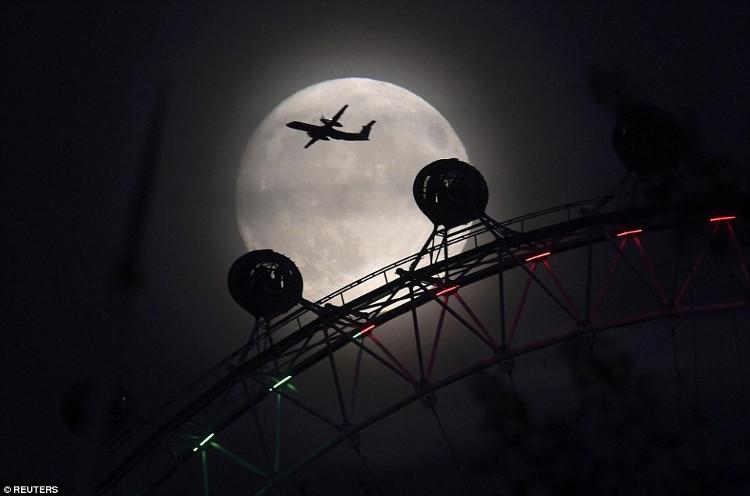 Một phi cơ bay trên nền trời trăng rằm ở thủ đô London của Anh.