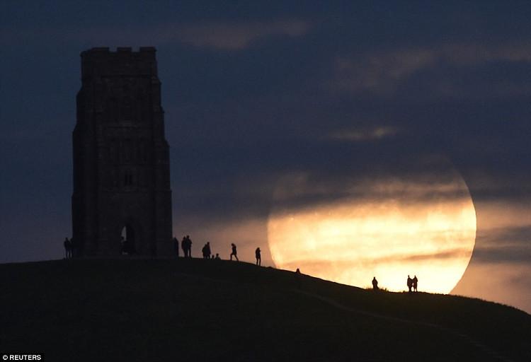 Người dân thị trấn Glastonbury quan sát mặt trăng dần mọc trong đêm 13/11.