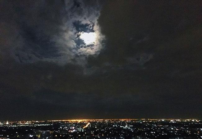 Siêu Trăng chưa tròn hẳn vẫn ẩn hiện sau lớp mây ở Bangkok.