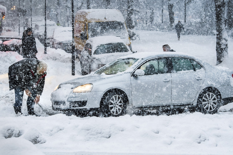 Một người đàn ông đang dùng xẻng dọn tuyết trên đường.