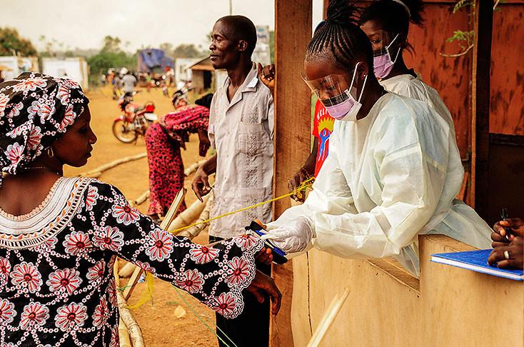 Nhân viên y tế Sierra Leone kiểm tra thân nhiệt của hành khách tại khu vực biên giới với Liberia ở Jendema