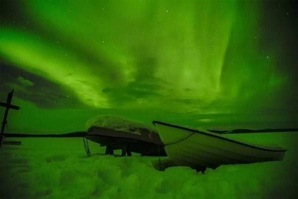 Những chiếc thuyền trên nền tuyết trắng dưới ánh sáng cực quang.