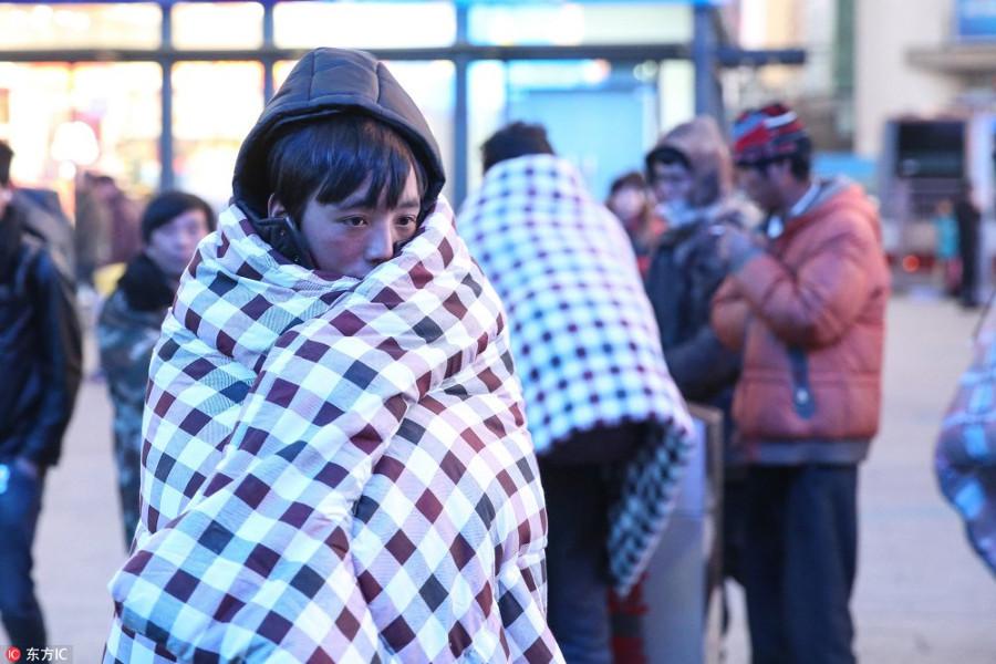 Những người dân xa quê trùm chăn bông cho đỡ lạnh khi đứng chờ tàu ở ga Bắc Kinh.